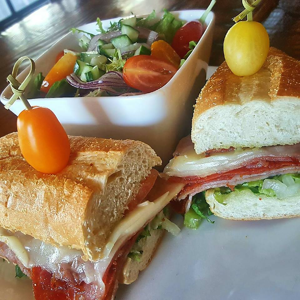 italian sub with tomatoes and a side salad