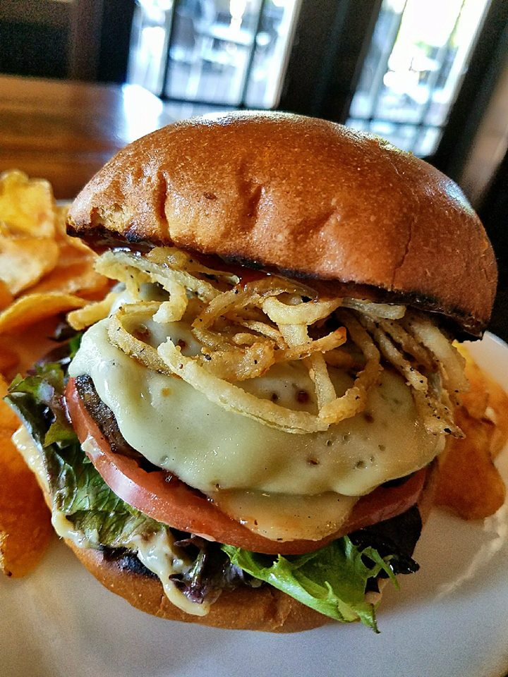 cheeseburger with lettuce, tomato topped woth crispy onions and a side of chips