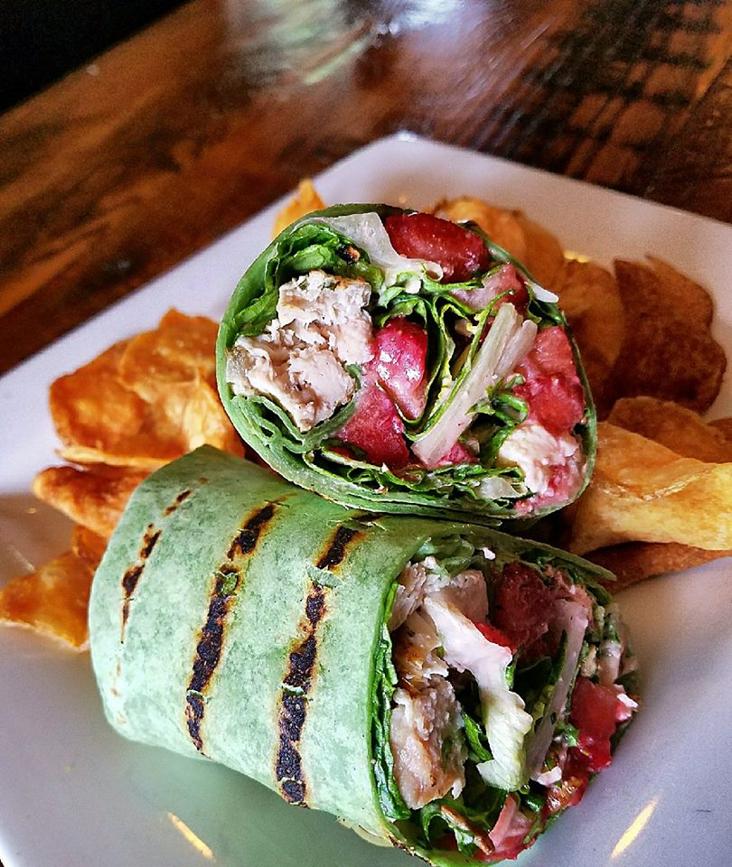 chicken wrap with lettuce, tomatoes with a side of chips