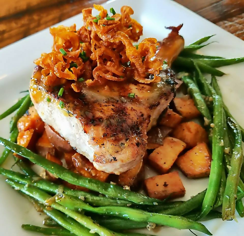 cooked fish over potatoes with crispy onions and asparagus