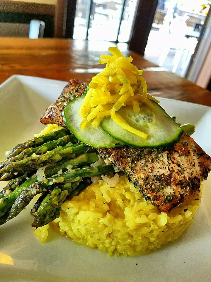 cooked fish over rice with asparagus and cucumbers
