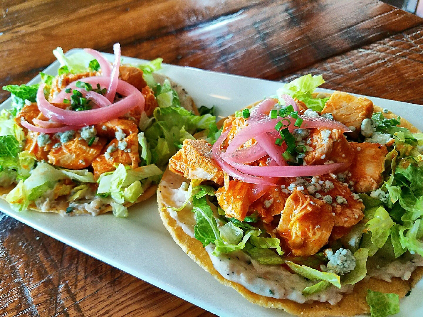 two large fish tacos with vegetables and sauce