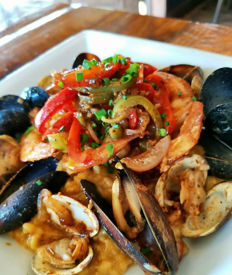 bowl of cooked shrimp, mussels and clams covered in sauce