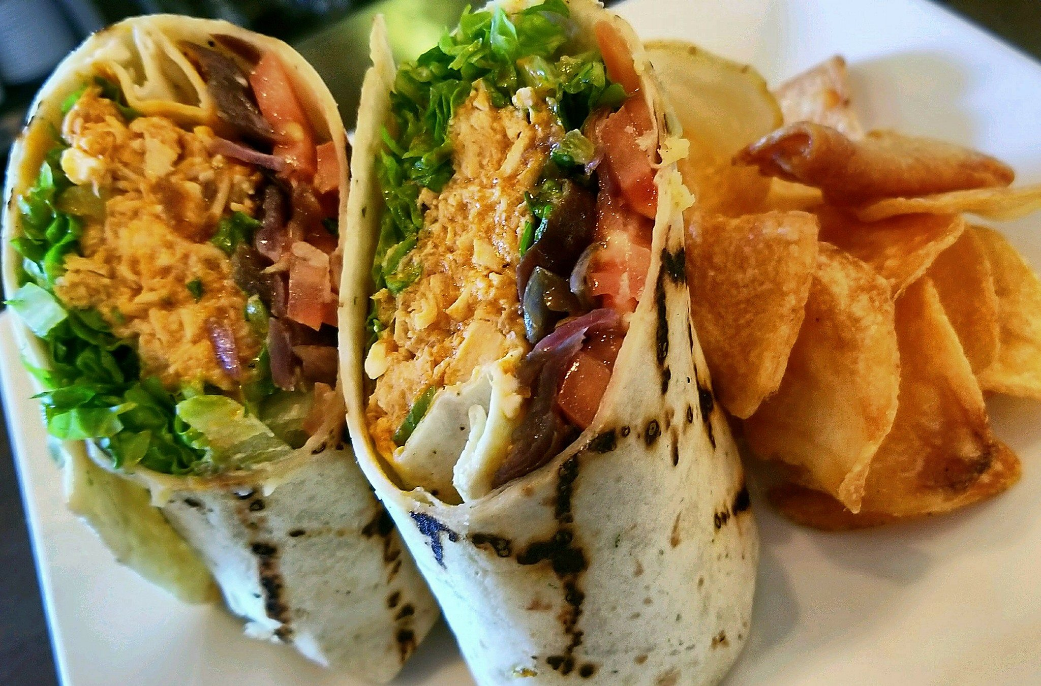 chicken wrap with beans, lettuce and tomatoes with a side of fries