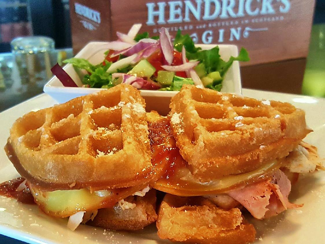 egg sandwich between waffles with a side salad