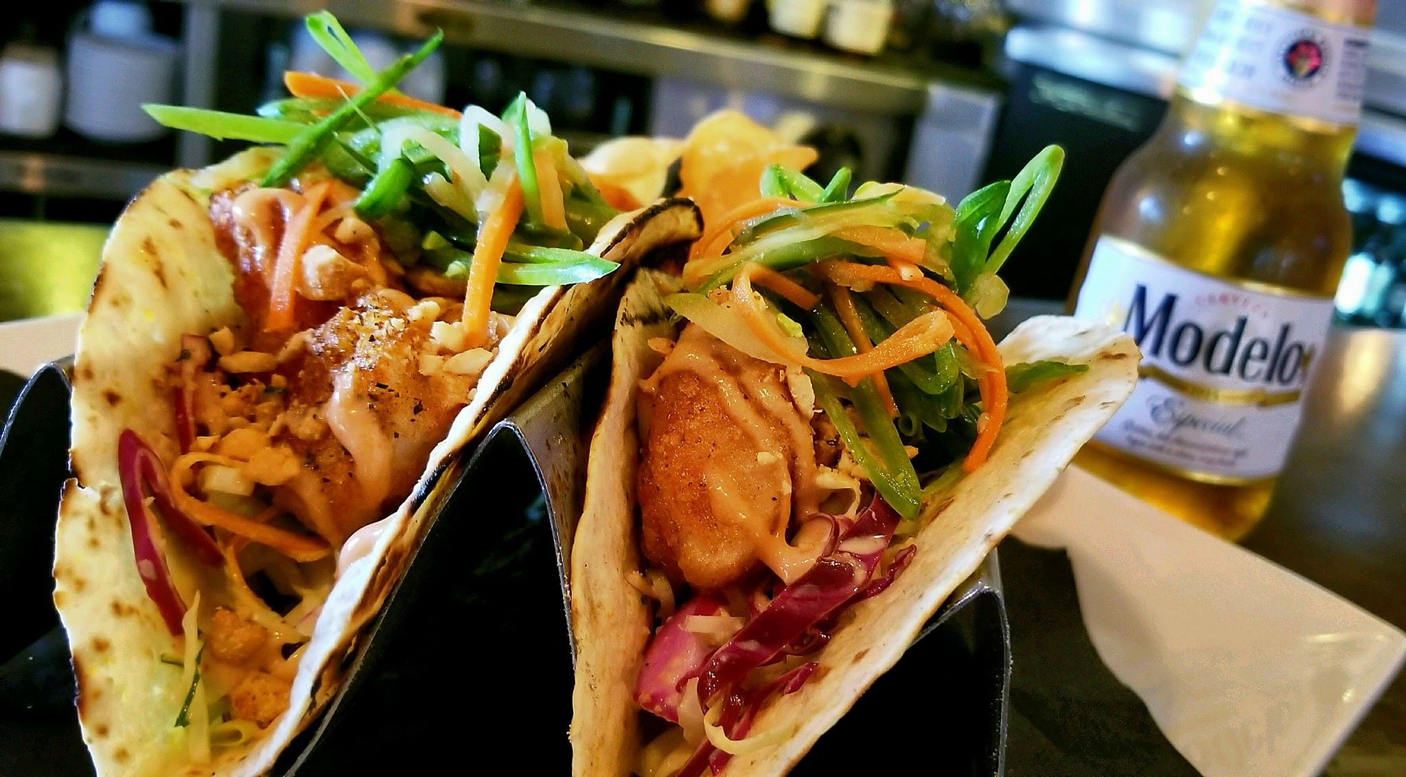 soft shell tacos in metal holders topped with sauce and coleslaw