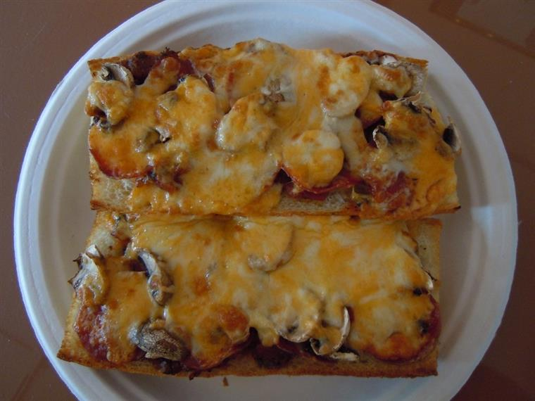 Toasted sandwich open-faced with mushrooms, pepperoni, melted cheeses
