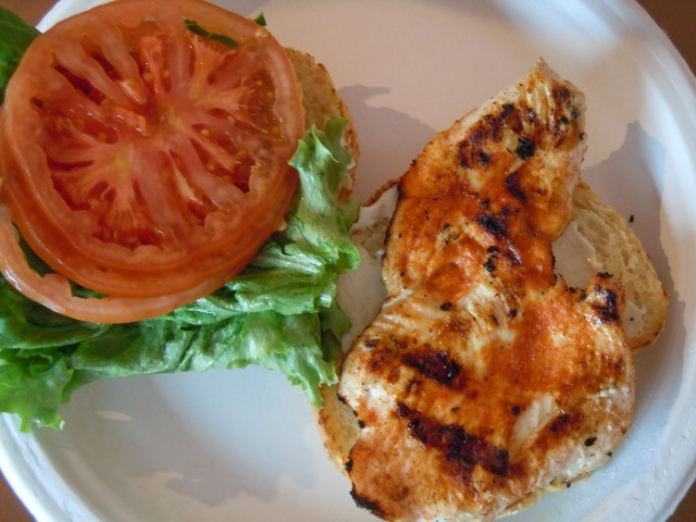 Grilled chicken breast sandwich open-faced with tomatoes and lettuce.