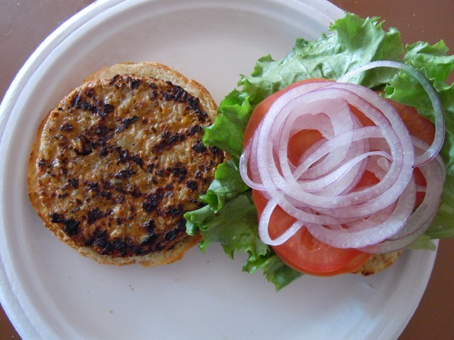 Open-faced burger pattie with lettuce, tomato, onions.