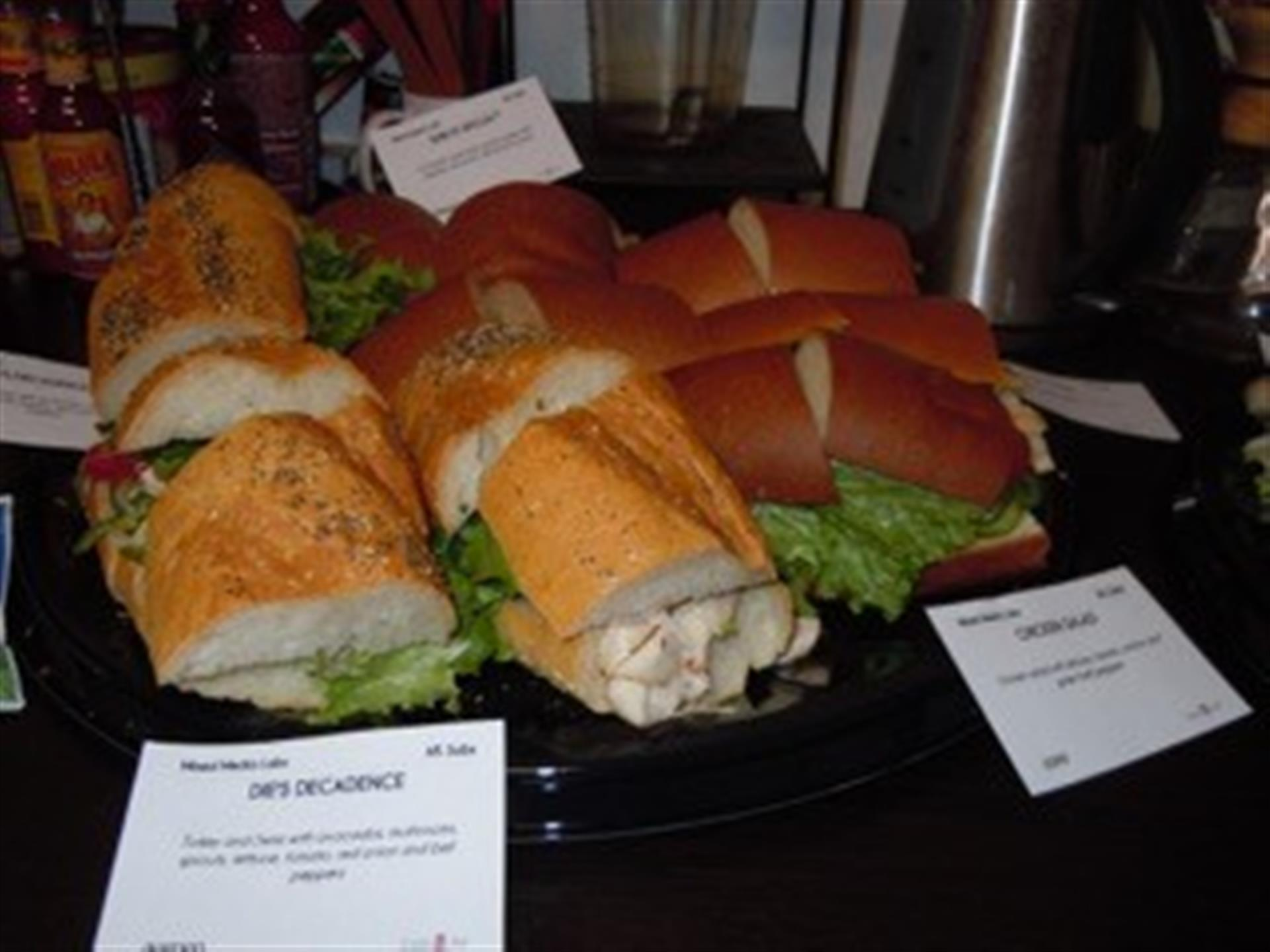 Turkey and Swiss sandwiches with chicken salad sandwiches on black trays.