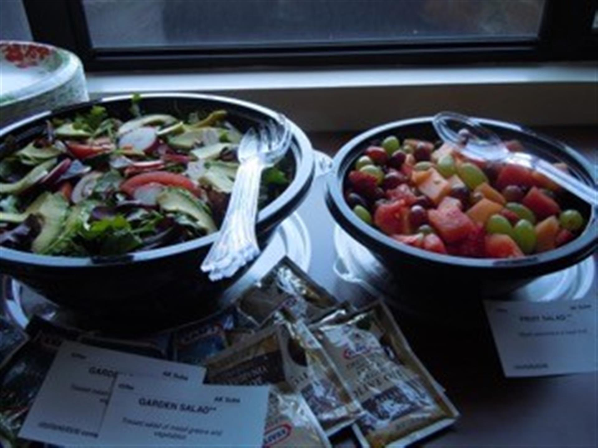 Bowls of salad, fruit salad with dressings on table.