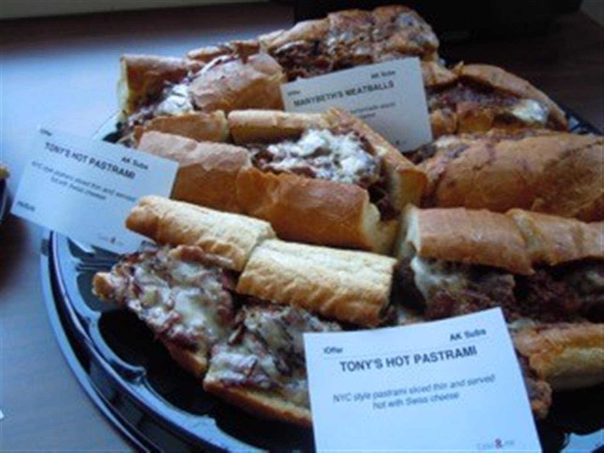 Pastrami and meatball sandwiches on black tray