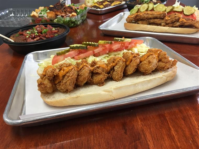 photo of a hero with fried shrimp, chipotle sauce, lattuce, tomato, and pickles on it with the same sandwich in the background on a wooden surface