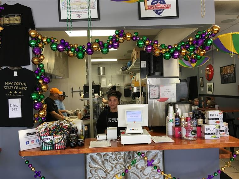 the check out area with a woman working behind the register and mardi gras themed decorations lining the check out area