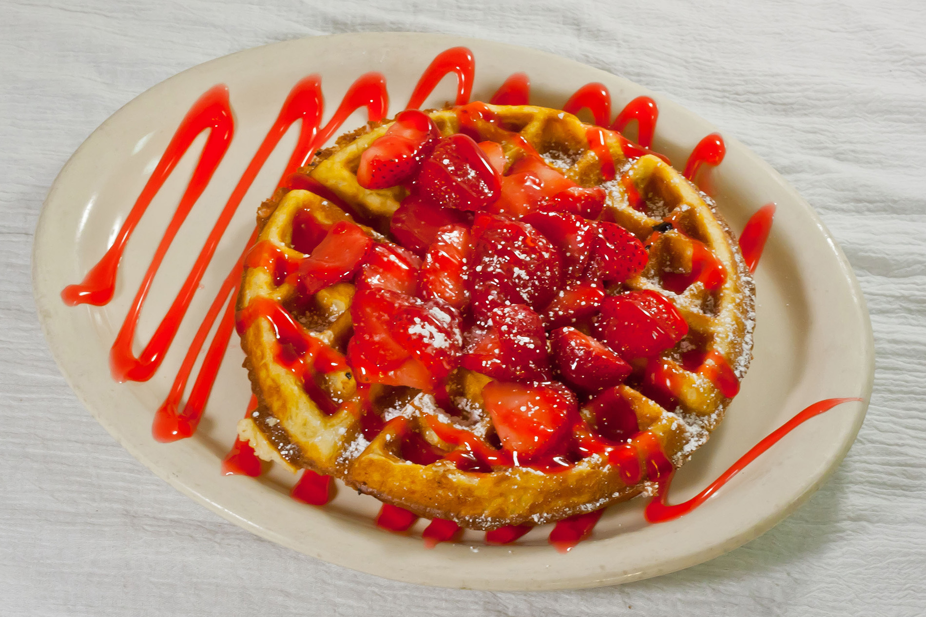 waffle on a plate covered in strawberries, strawberry syrup and powdered sugar