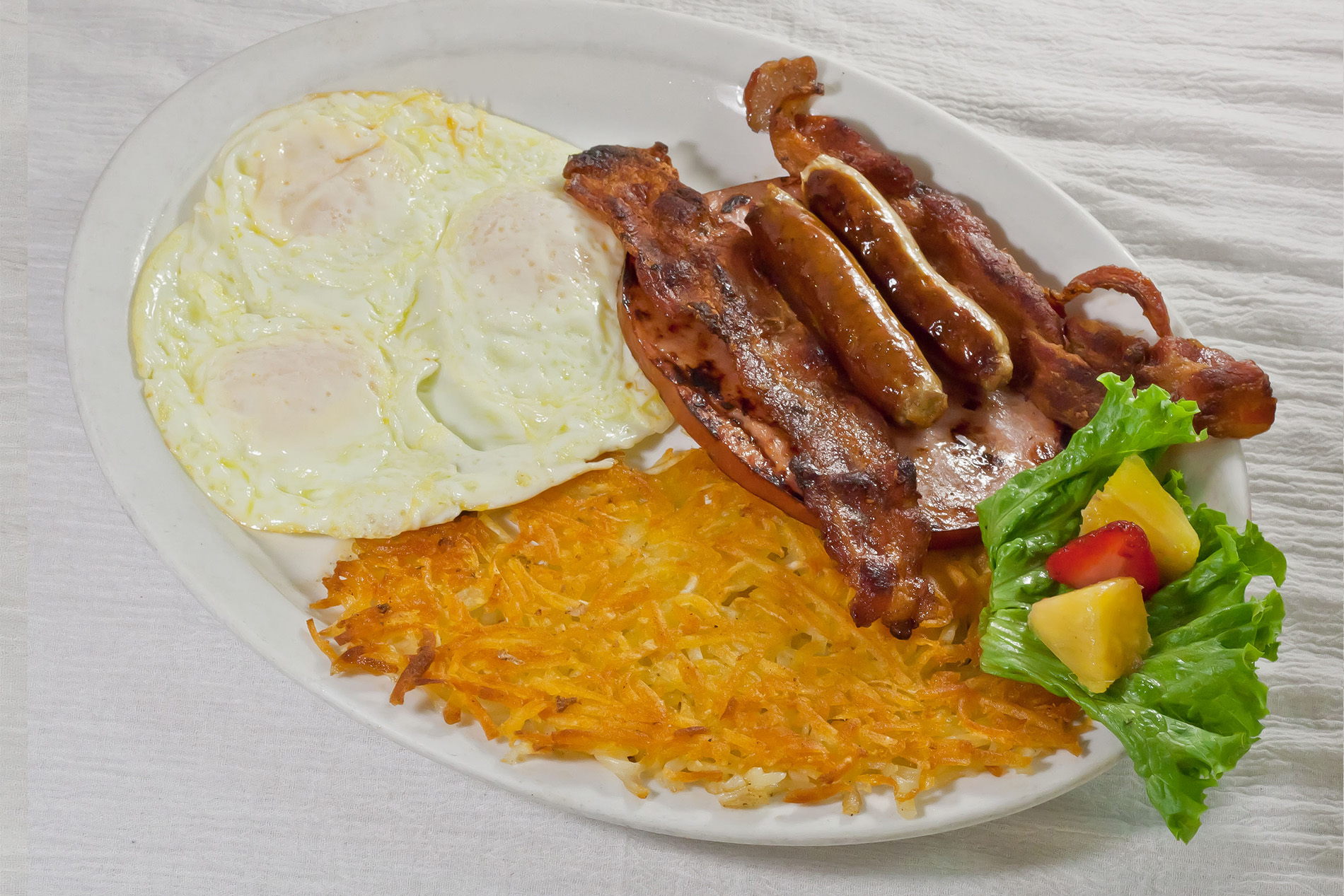 plate of hashbrowns, three fried eggs, bacon, ham and sausage