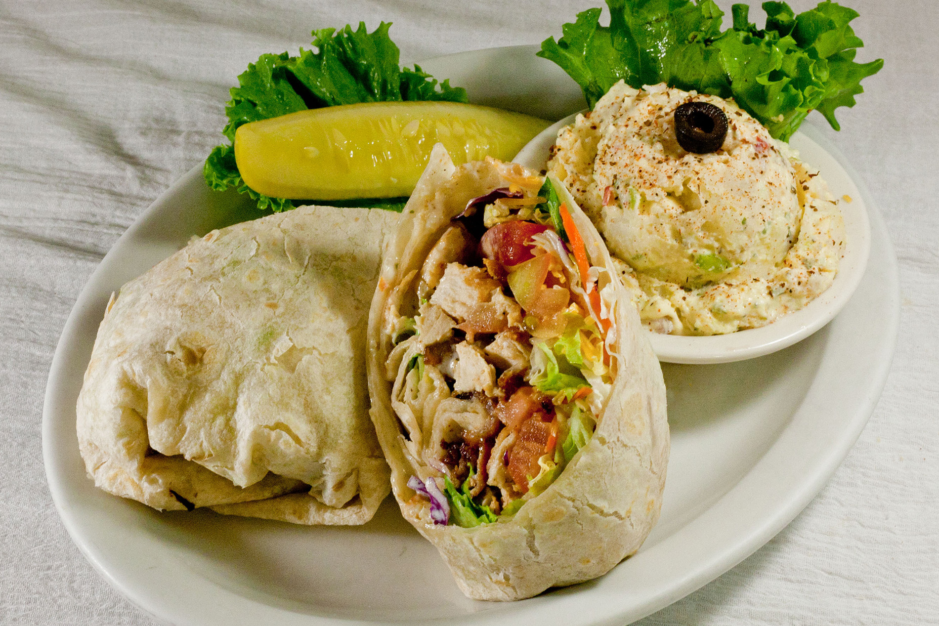 california chicken wrap with chicken, tomato, bacon, lettuce and cheese, side of potato salad