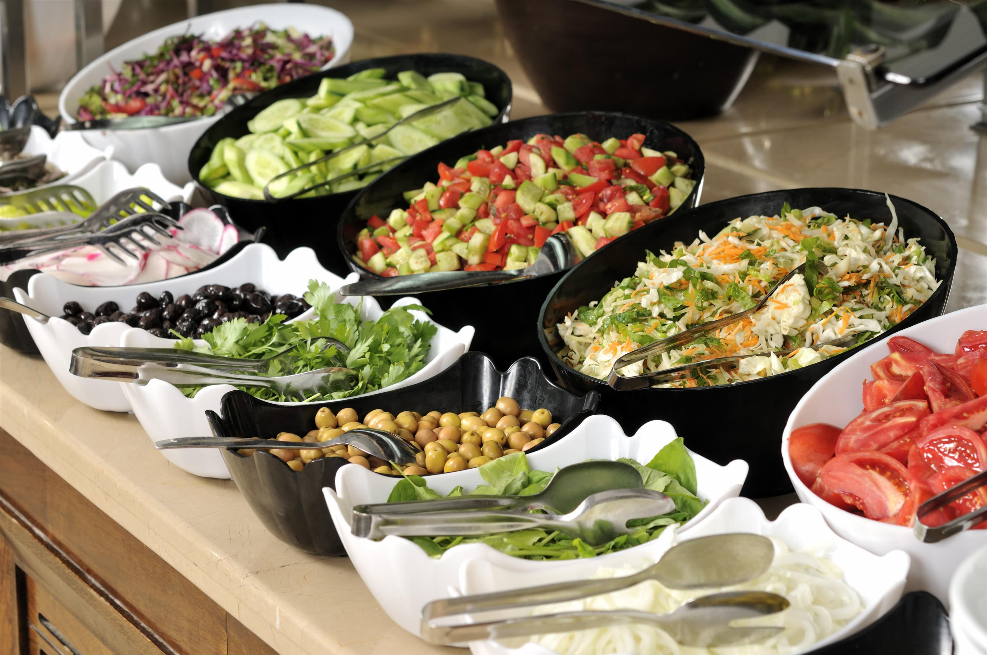 salad bar with bowls of lettuce, olives, cucumber. tomato, spinach, and onion