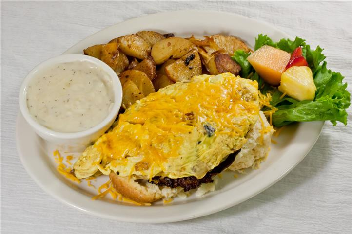 Country Skillet. Three eggs scrambled with bell peppers and onions. Served on top of a fresh biscuit and sausage patty topped with country gravy. Served with your choice of home fries or hash brown.
