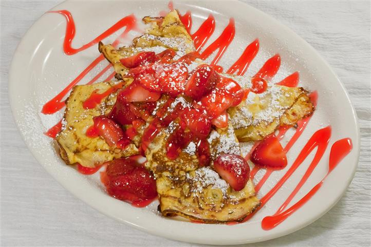 French toast with strawberries, topped with powdered sugar.
