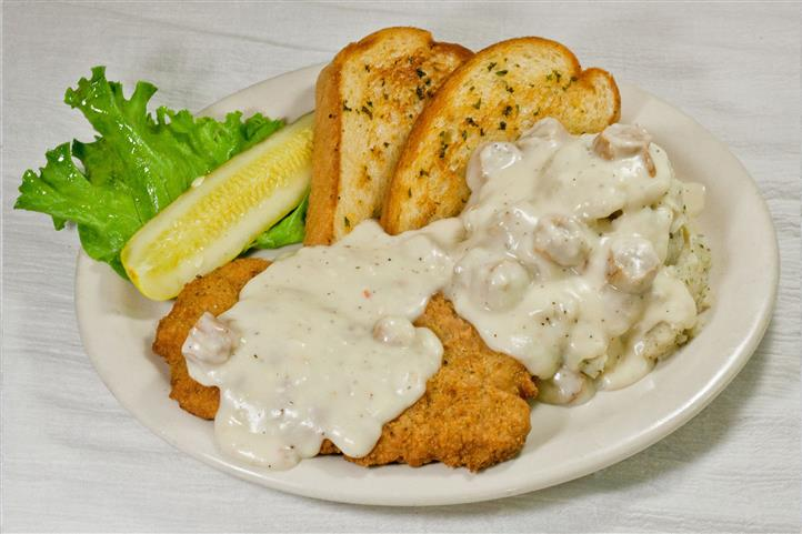 Country fried steak with gravy and toast.