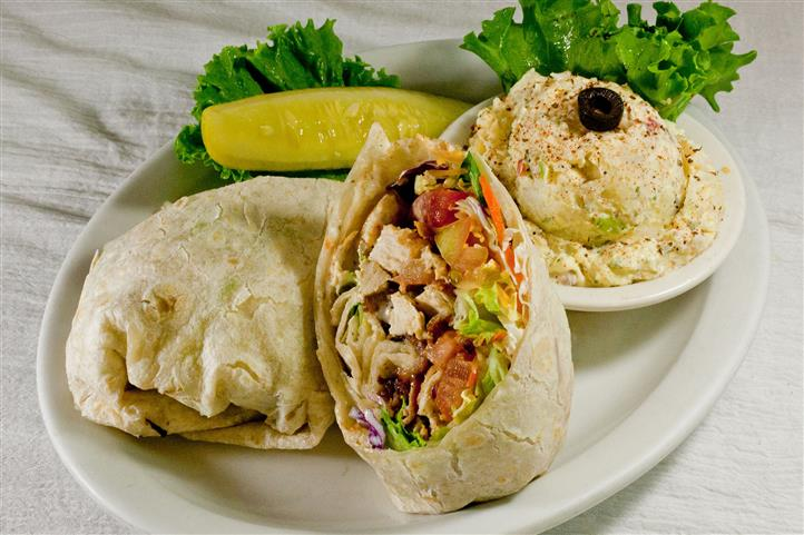Ranch chicken and bacon wrap. Grilled chicken breast, bacon, tomatoes, cheddar cheese, ranch dressing, and fresh greens all wrapped in a large flour tortilla and served with your choice of side.