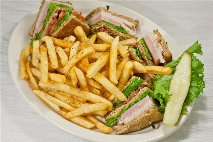 Chef's Club Sandwiches - ham, turkey, bacon and tomato on wheat bread served with house seasoned fries and pickle.