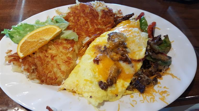 Omelet with meat, peppers, hash browns on dish.