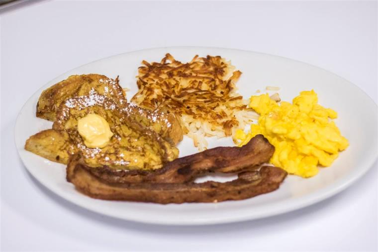 Scrambled eggs with french toast, hash browns, bacon.