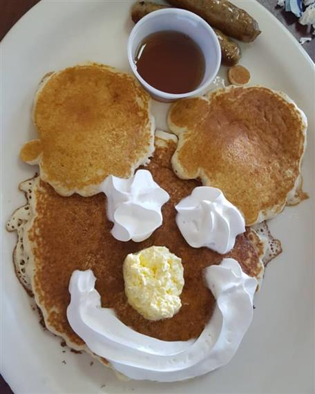 Pancakes on dish with whipped cream and butter in shape of face.