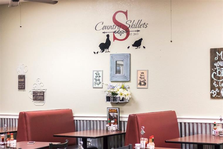 Country Skillets sign on dining room wall with framed pictures and slogans above dining booths.