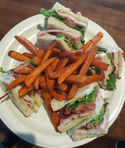 Chef's club sandwich. Ham, turkey, bacon, lettuce, tomato on white bread with sweet potato fries.
