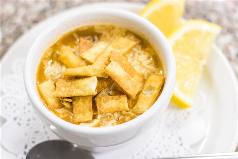 Cup of chicken tortilla soup, lemon wedges on dish beneath as garnish.