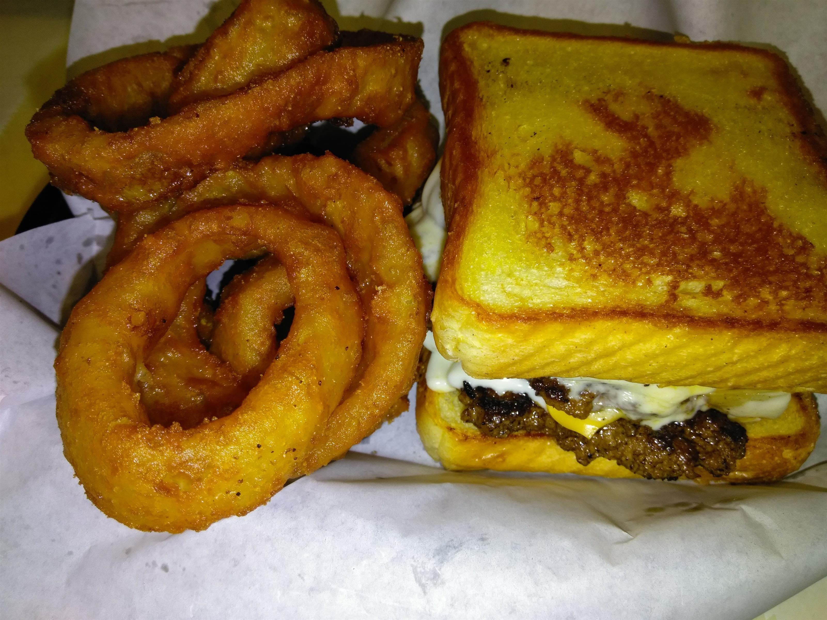 A cheese burger on toast with a side of onion rings
