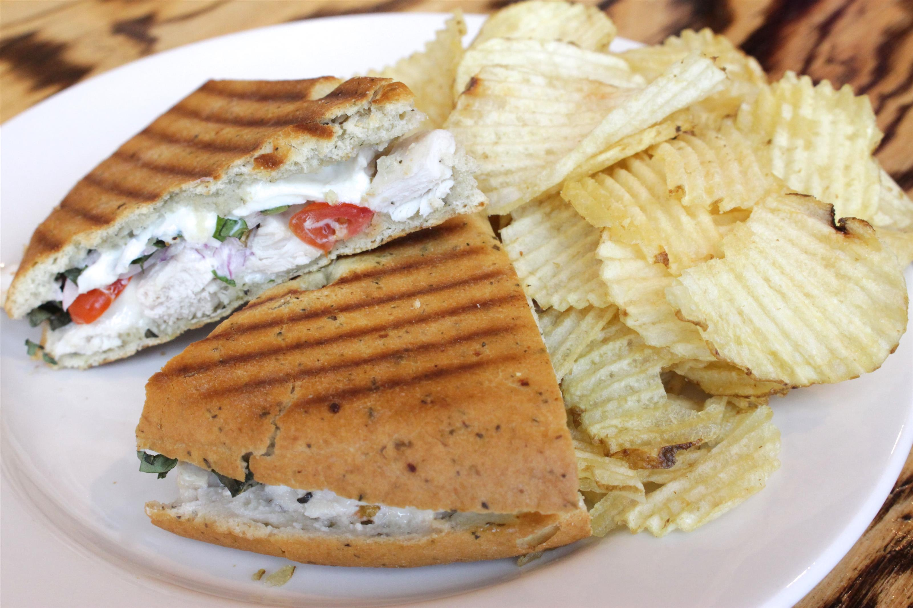 Flatbread sandwich with side of chips.