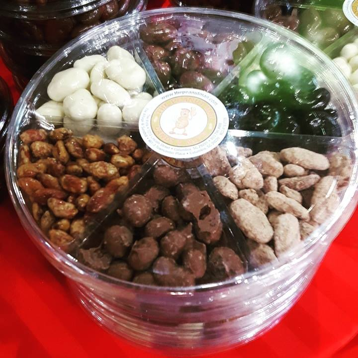 Various chocolate and candied nuts in plastic container.