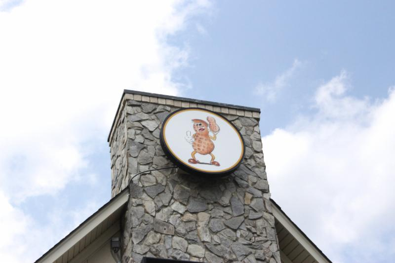 The Peanut Man sign atop chimney structure on exterior of building.