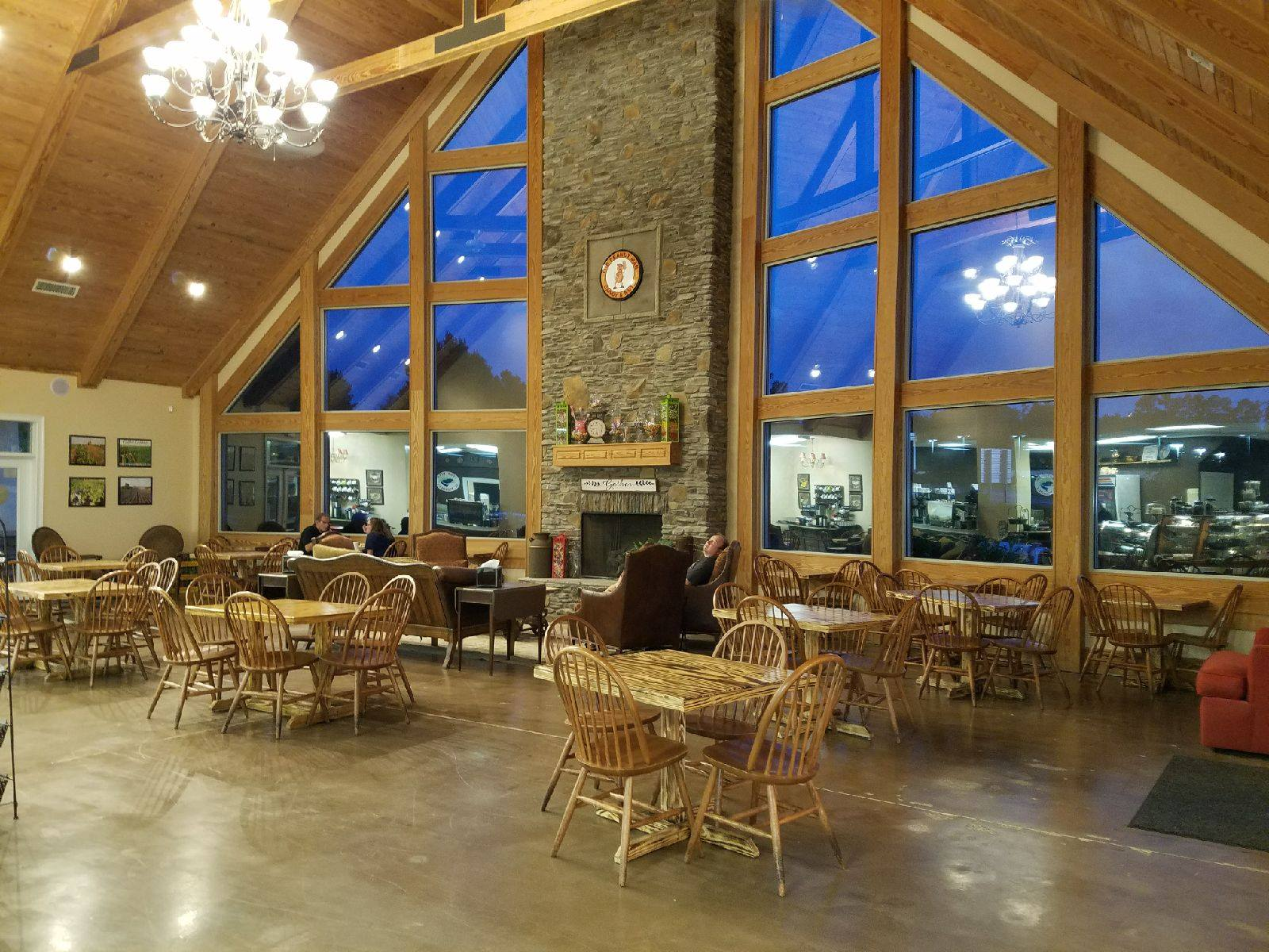 The Peanut Man dining area. Wood chairs and tables in front of large windows, under high ceilings