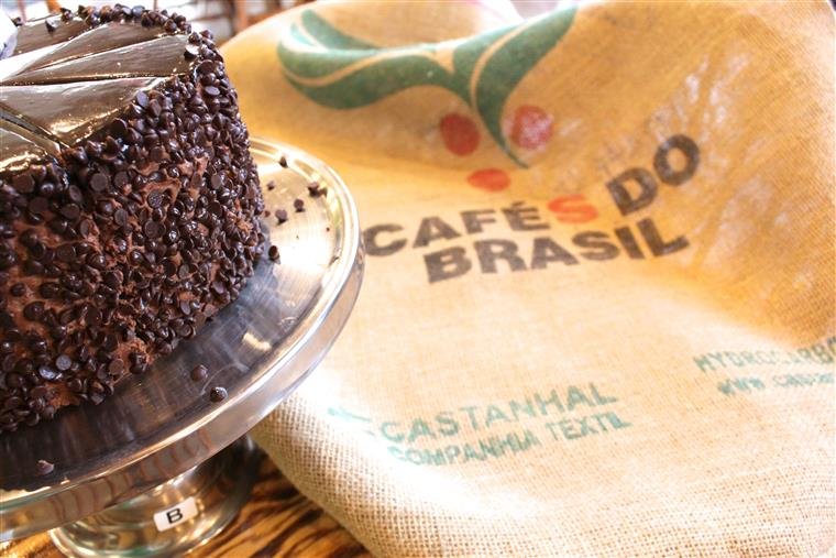 Chocolate cake on metal tray next to cafes do brasil bag.