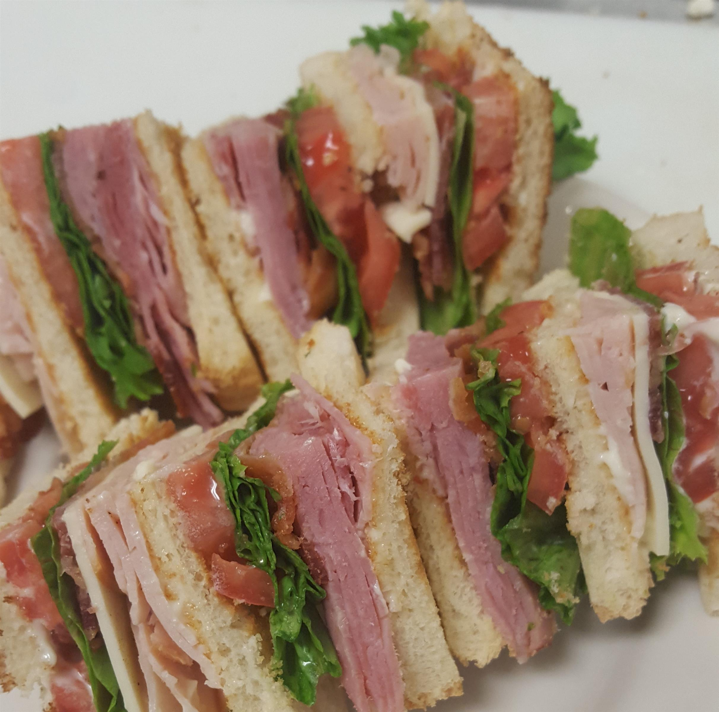 Classic Club sandwiches. Triple decker with shaved ham, smoked turkey, white american cheese, applewood bacon, mayo, green leaf lettuce, and vine ripe tomato.