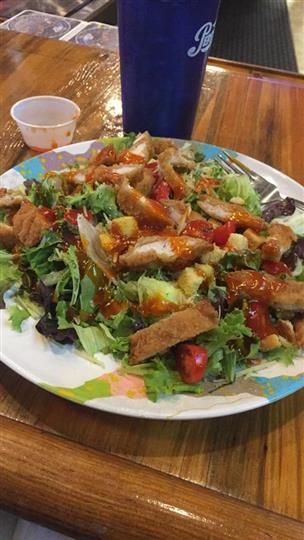 large salad with chicken slices and dressing
