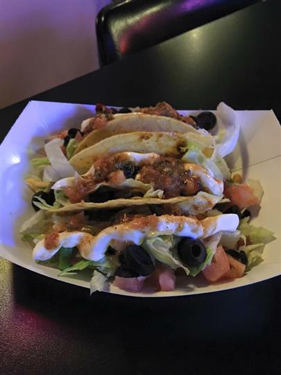 three soft shell tacos with olives, lettuce, tomatoes and sauce