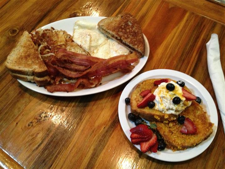 breakfast platters with pancakes, french toast, eggs, bacon and toast