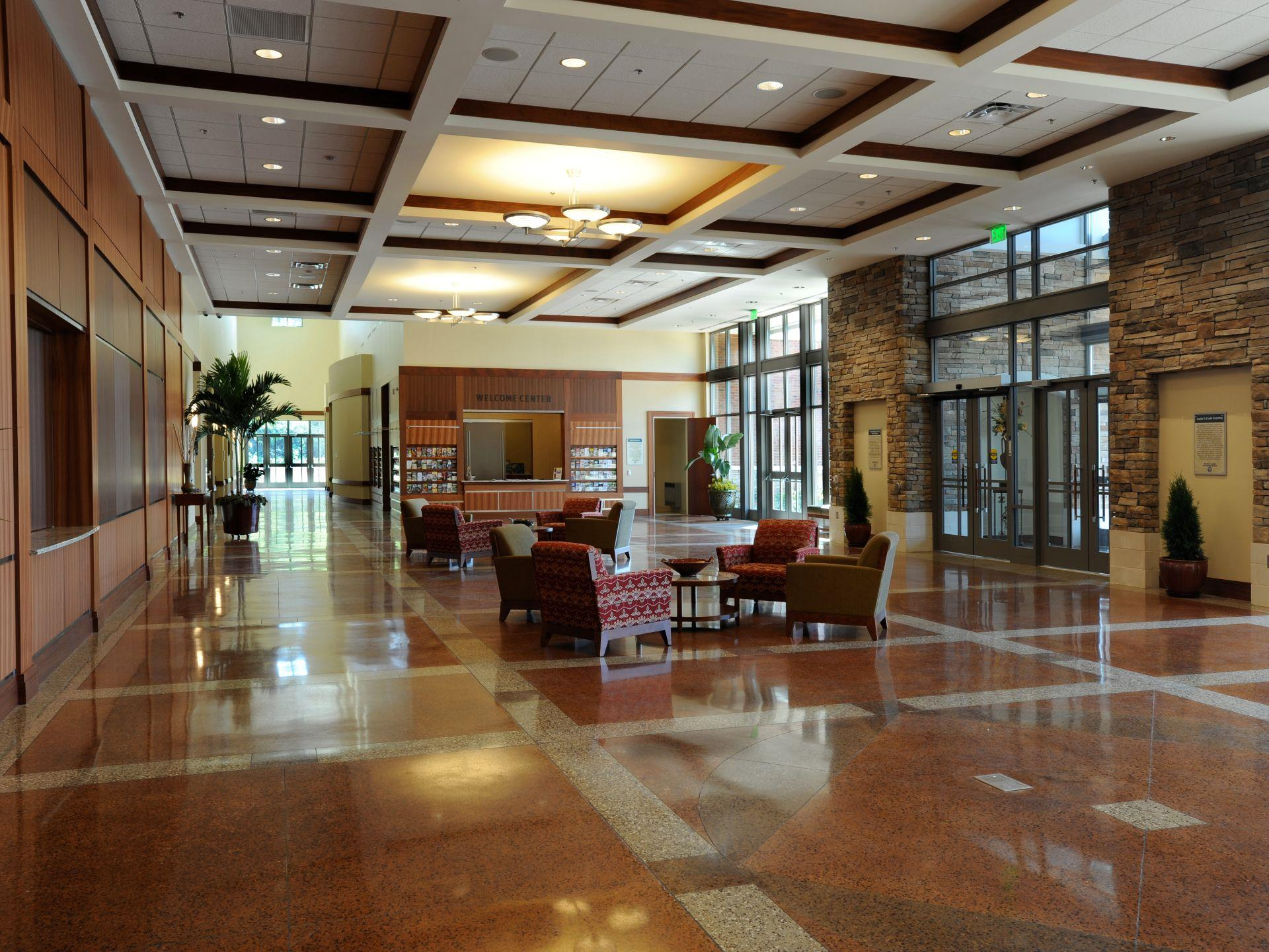 Interior lobby with stacked stone on one side amd wood paneling on adjacent wall with many windows sufficiently lighting the area