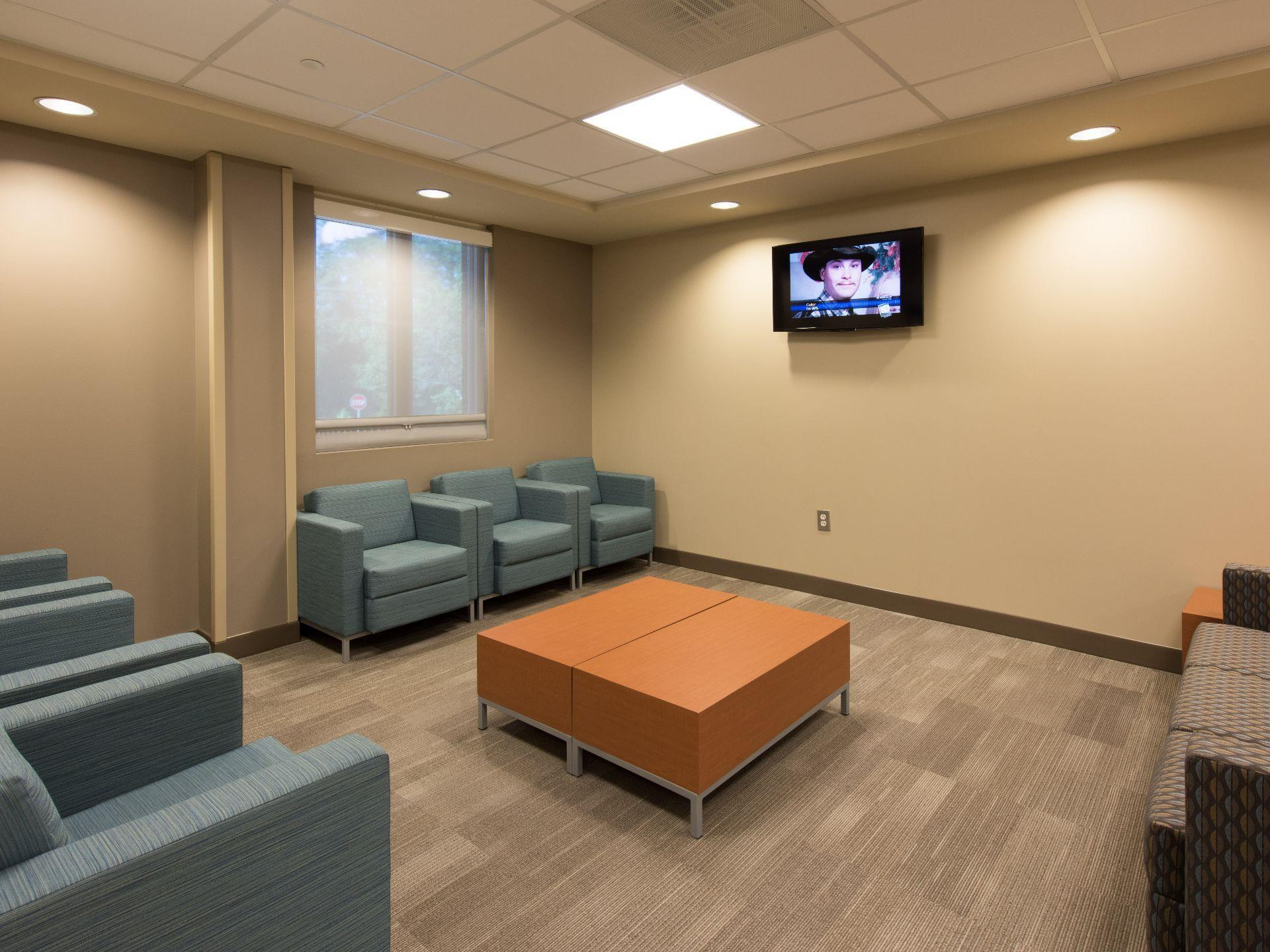 Waiting area with couches with coffee table and TV on wall.
