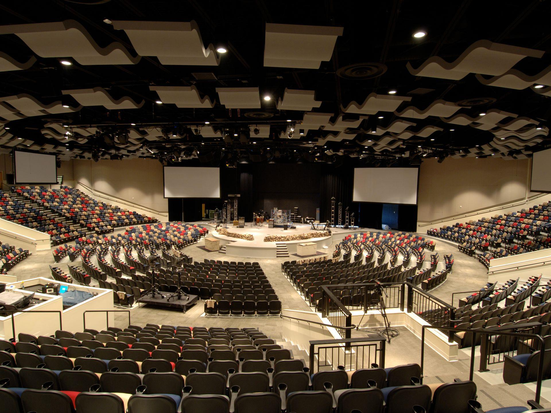 2,600-stadium seating worship center including a stage and wide screen TV monitors