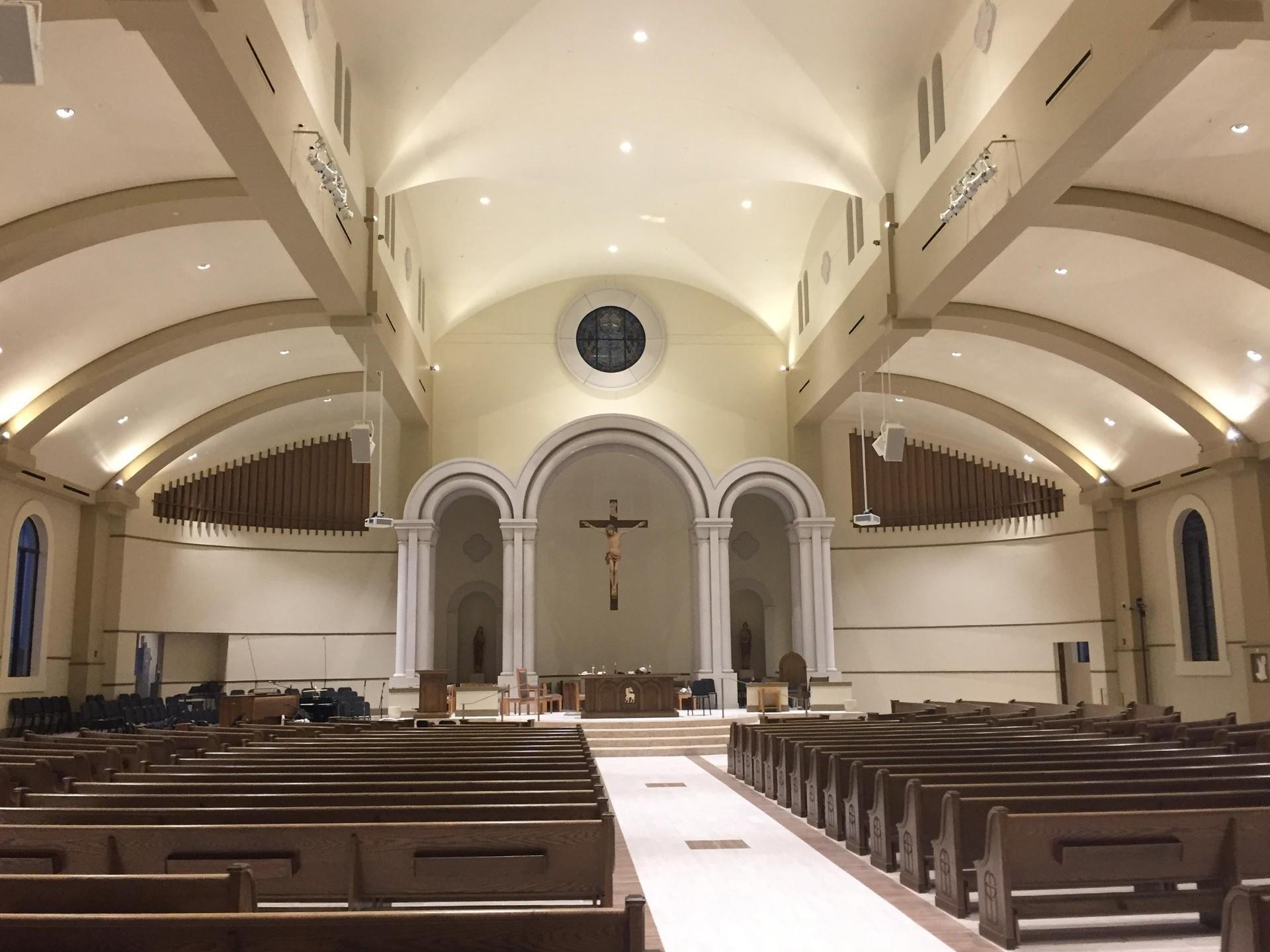Inside view of church aisle pews empty brightly lit.