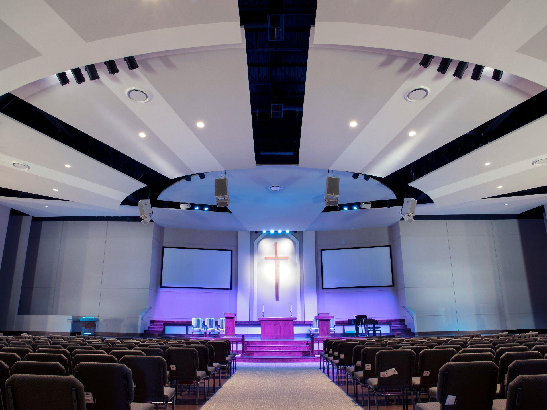View down the aisle to open stage lit up with purple lights and cross.