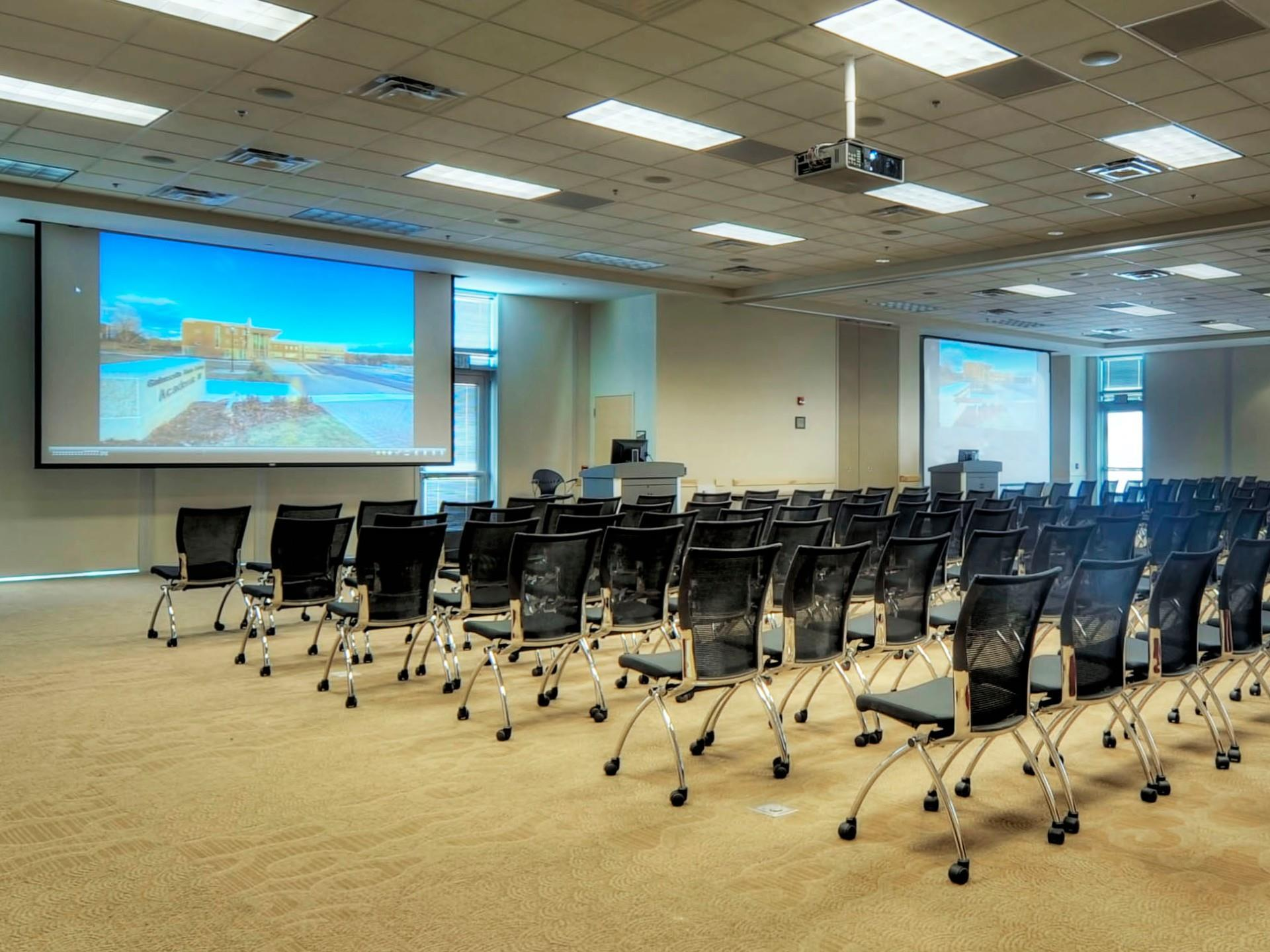 Instructional classroom with chairs and projector screen at front of the room with additional AV equipment