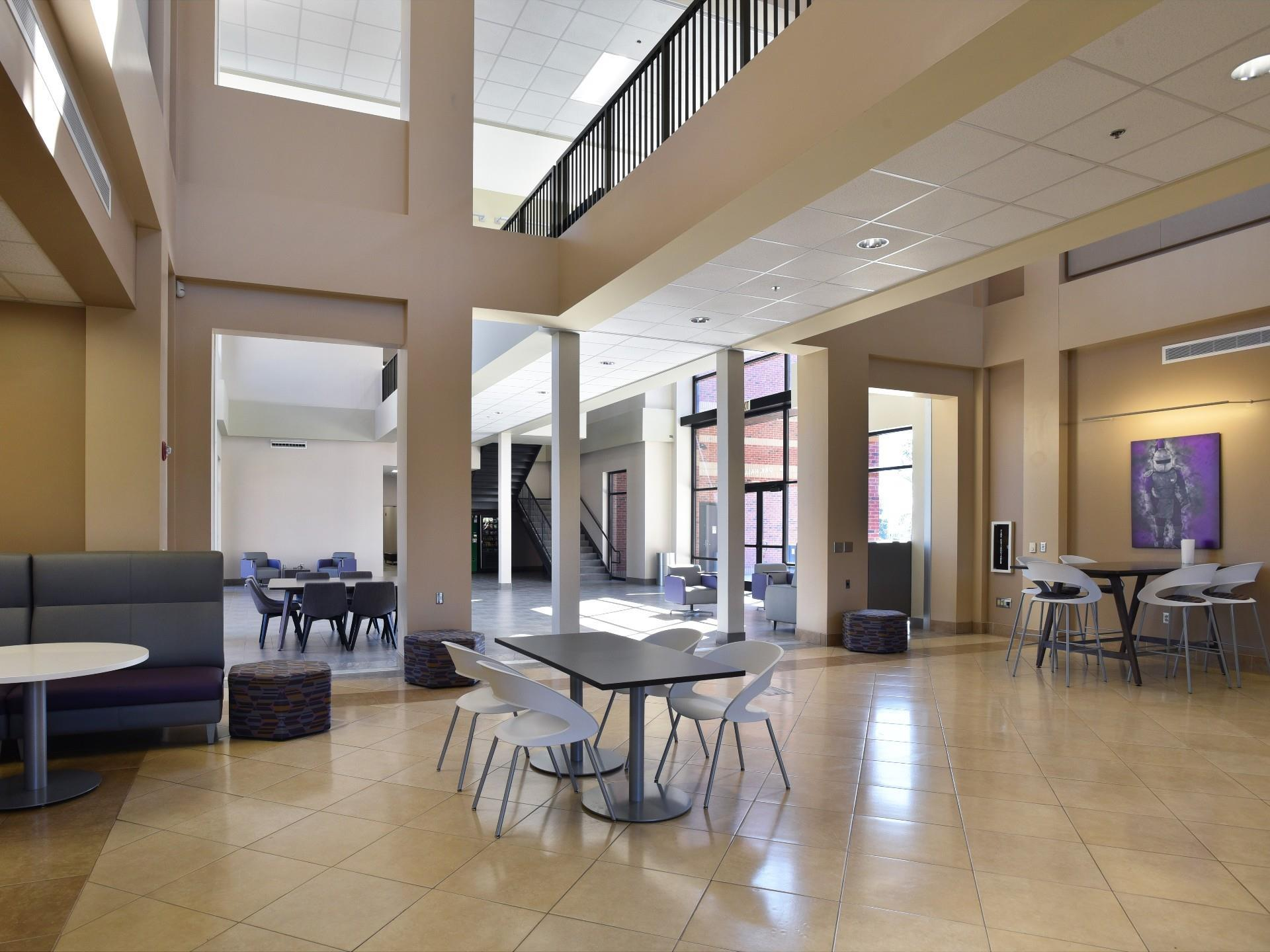 Interior of lobby/gathering space with tables and chairs and open concept with natural light.